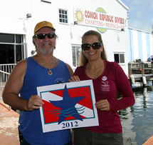 Florida Keys National Marine Sanctuary staff member LTjg Carmen Alex presents Conch Republic Divers owner Gary Mace with his charter's Blue Star decal and recognition.