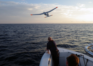 Photo of an unmanned aerial system flying over water.