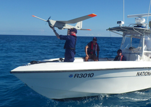 Photo of technician launching unmanned aerial system.