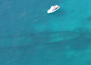 aerial view of A boat ties up to a mooring buoy