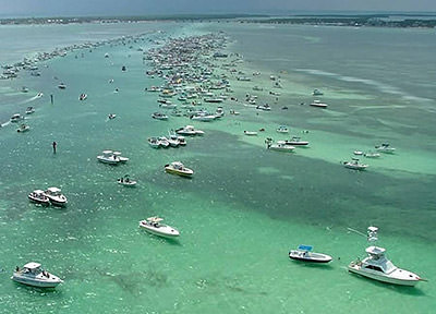 a large number of boats parked at a sand bar